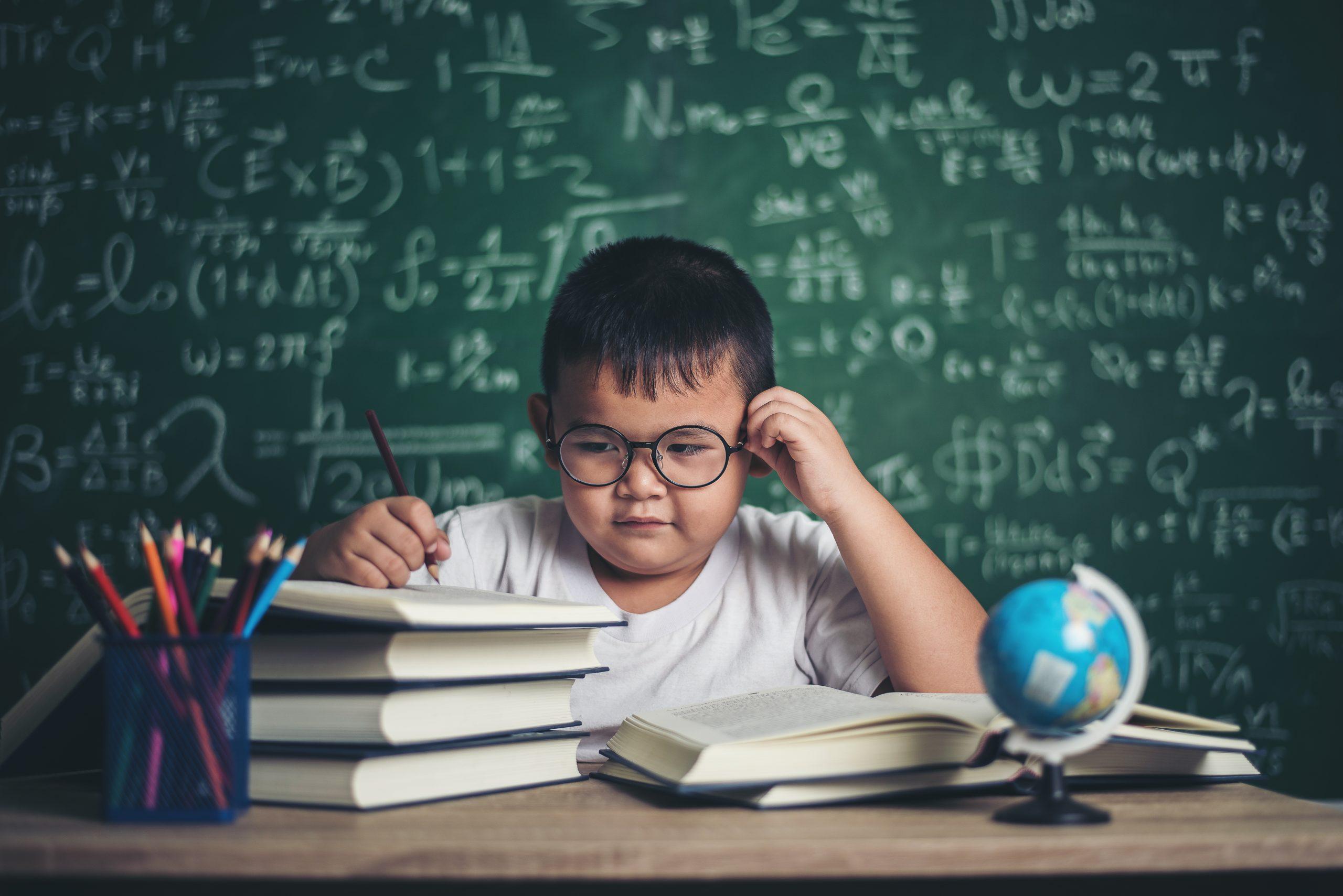 boy  write a book in the classroom.